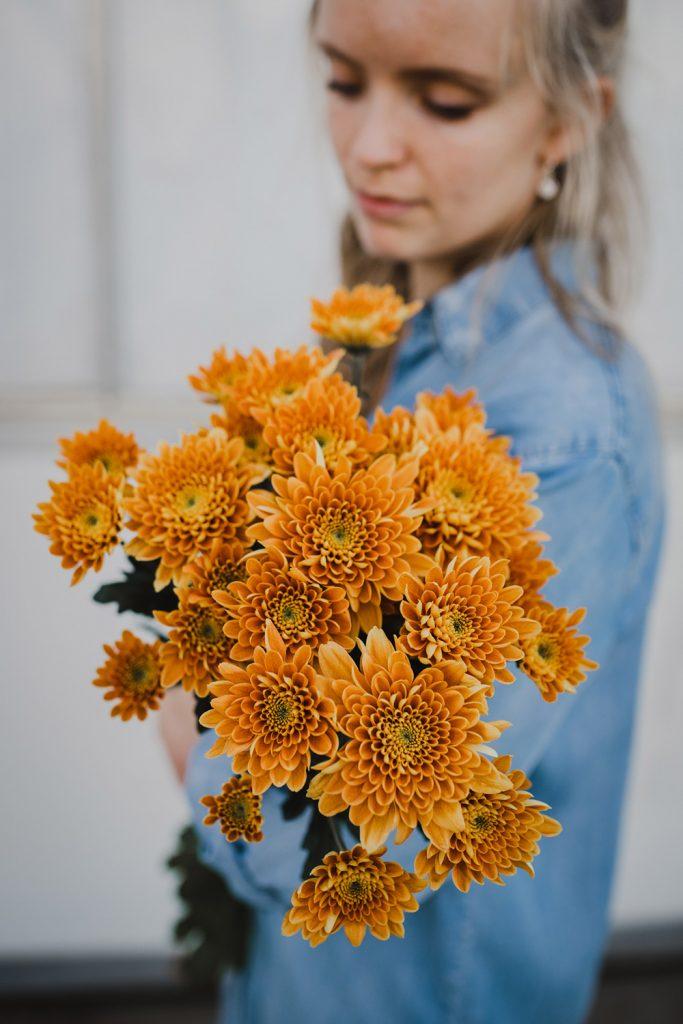 vrouw met bos bloemen voor chrysantenkwekerij kiepflower