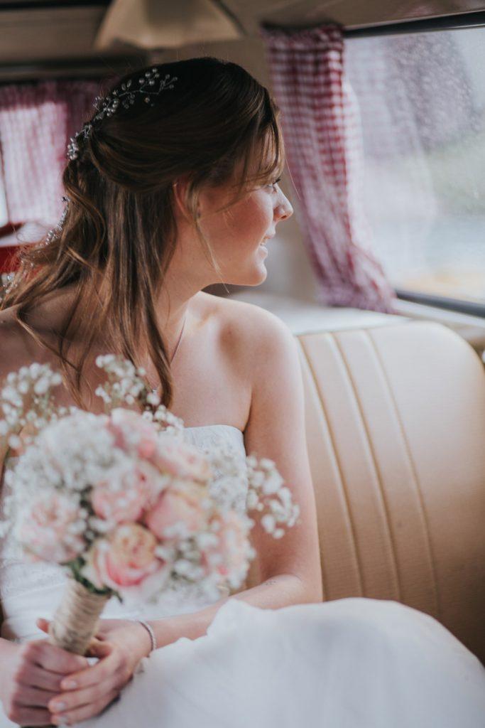 Bruid zit in Volkwagenbus en kijkt naar buiten