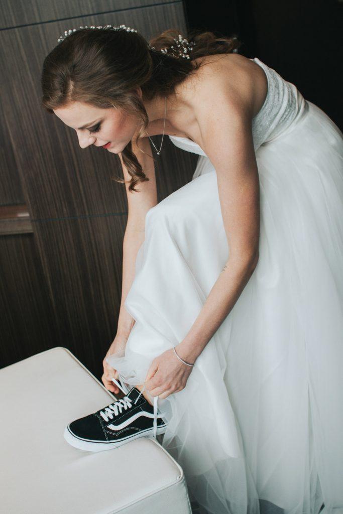 Bruid trekt sneakers aan onder bruidsjurk