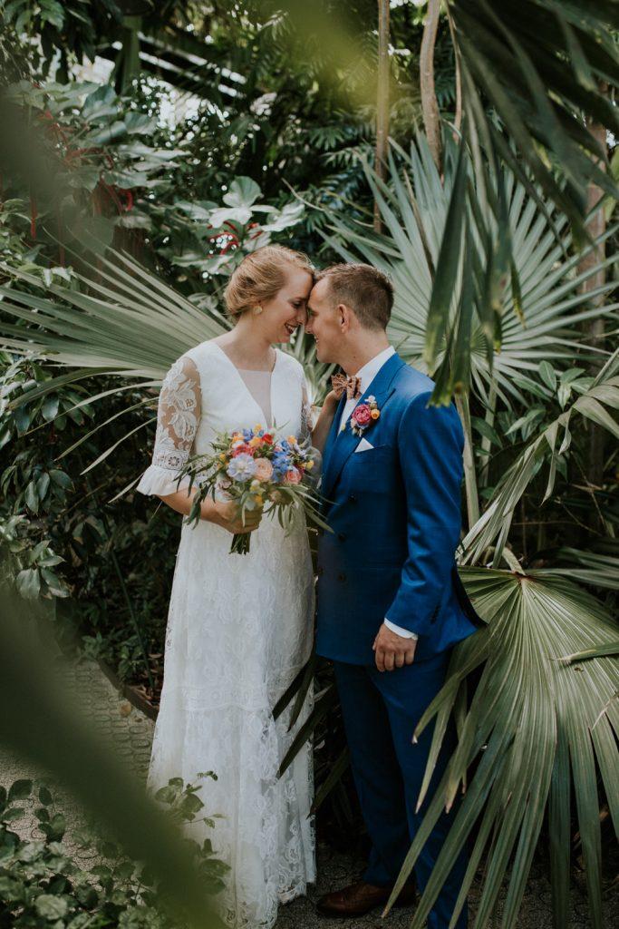 Bruidspaar staat in de botanische tuin in Leiden