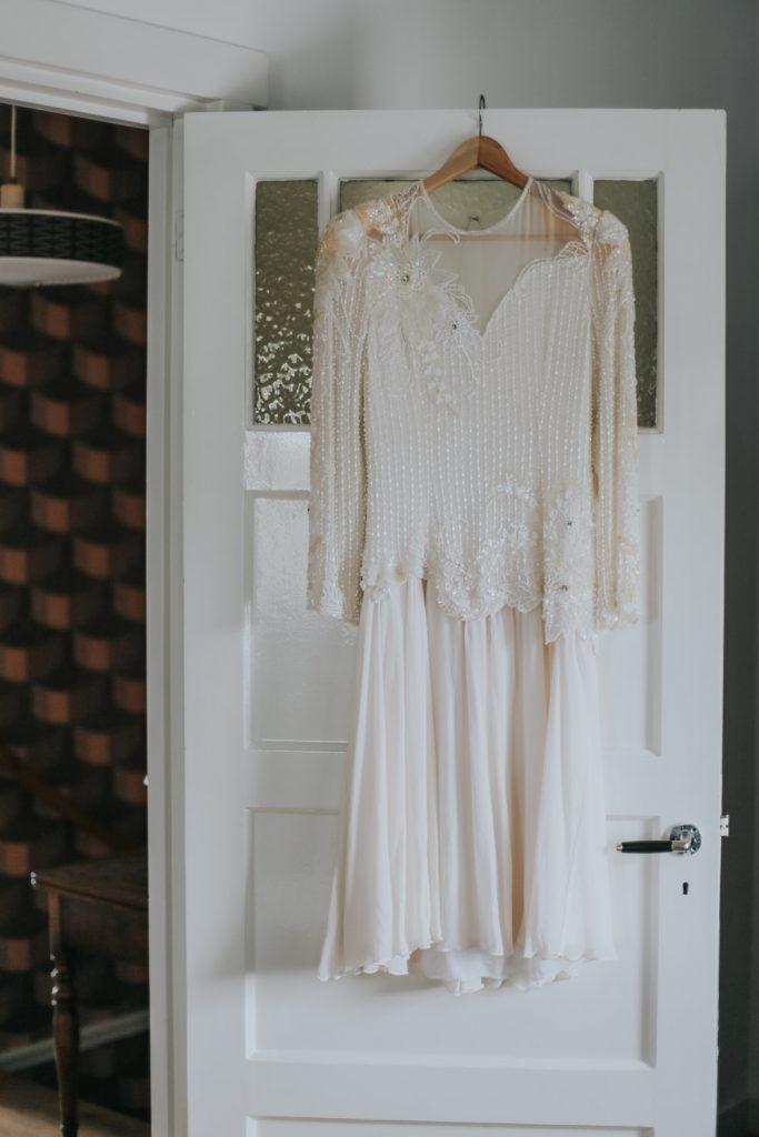 Vintage bruidsjurk hangt aan deur