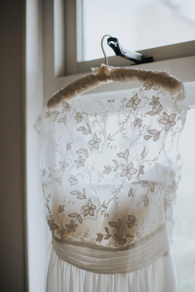 Bruidsjurk hangt aan raam
