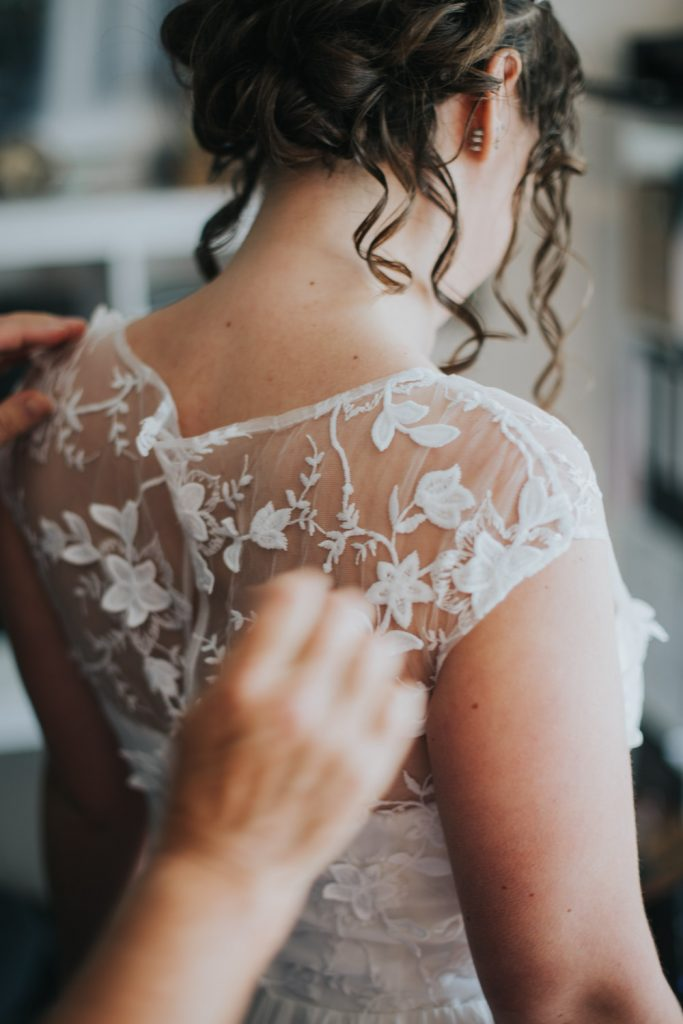 Bruid trekt bruidsjurk aan