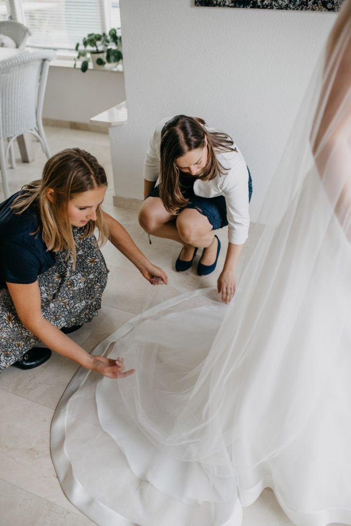 Vriendinnen helpen bruid met sluier