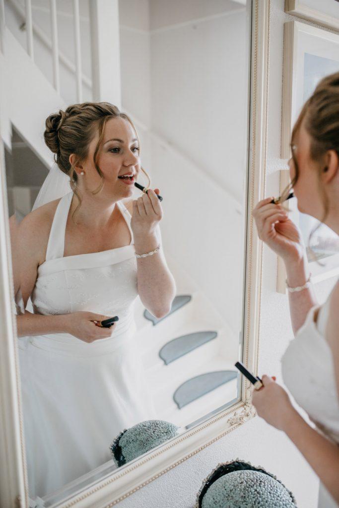 Bruid maakt zich op in spiegel