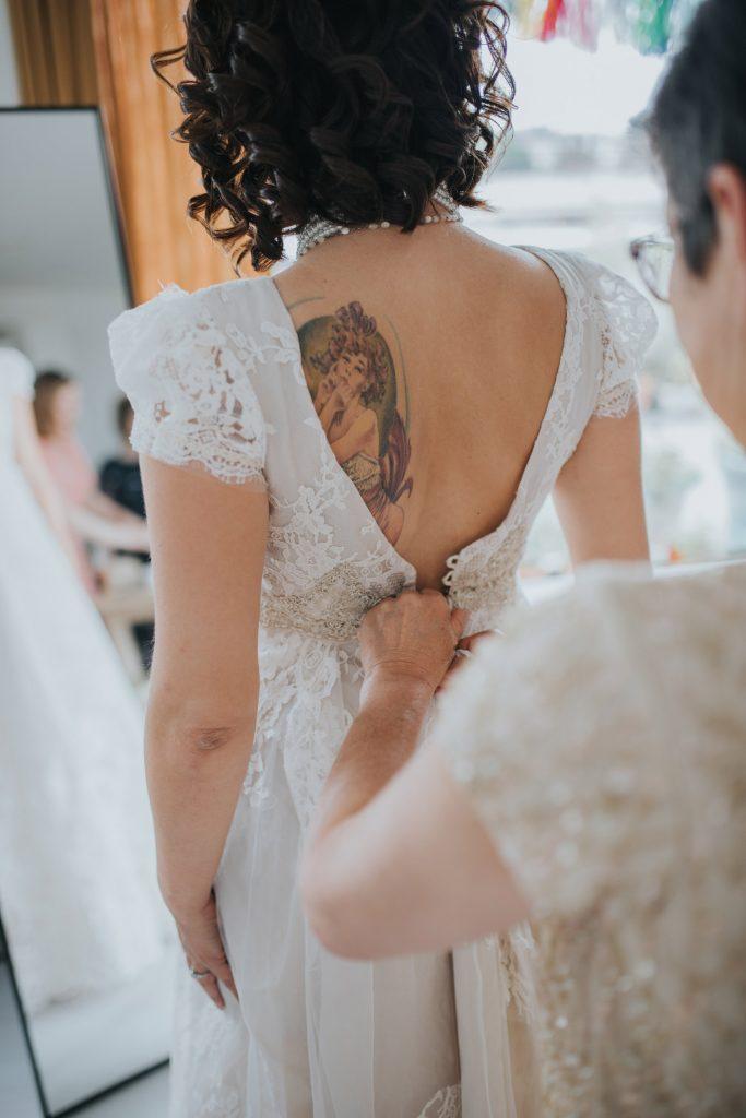 Bruid en moeder trekken bruidsjurk aan