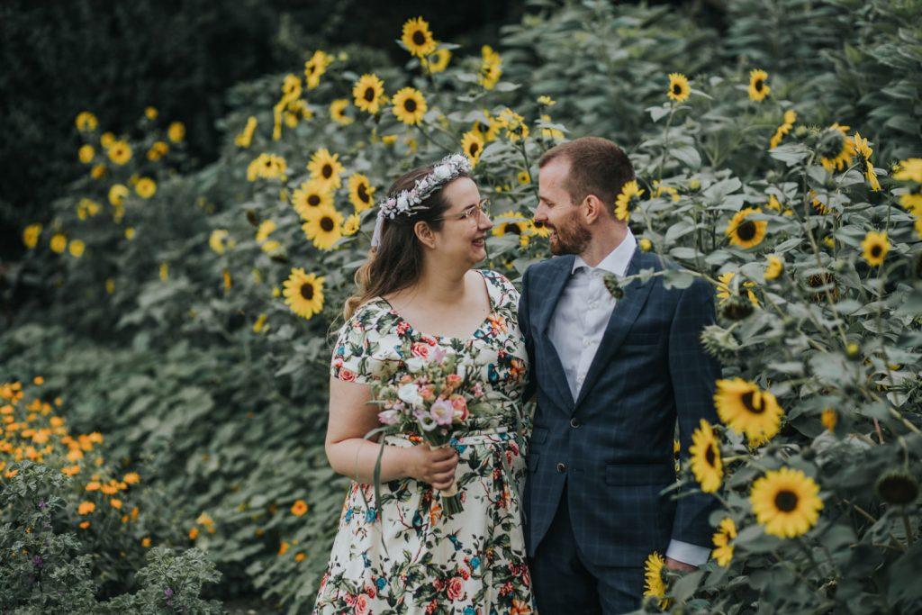 portret bruidspaar in een veld met zonnebloemen