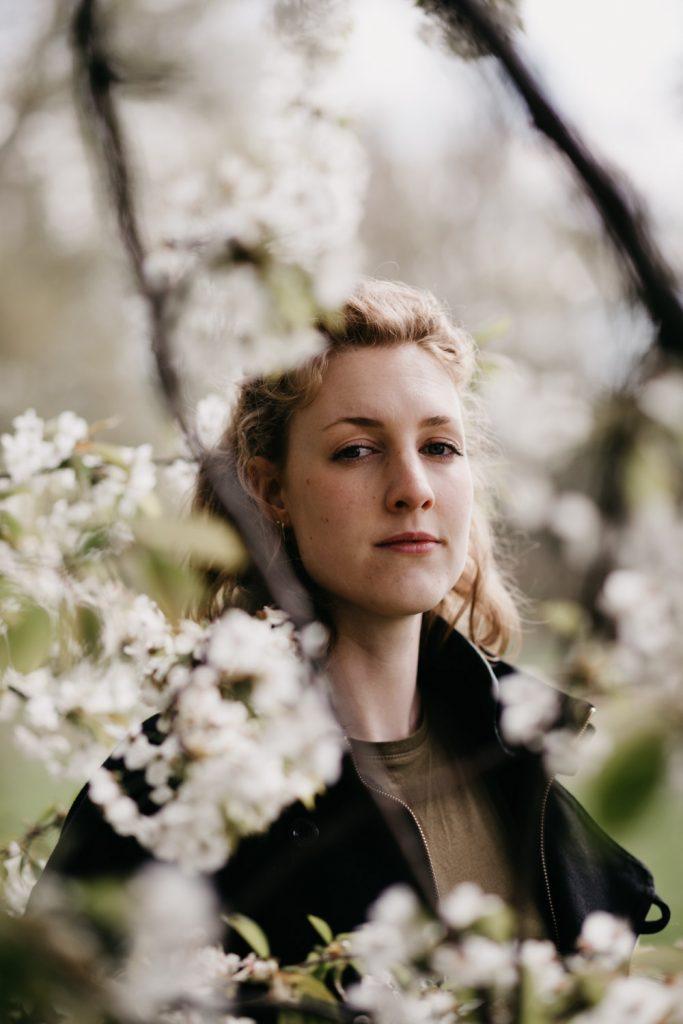 dromerig portret vrouw met bloesemboom, vrouw kijkt in camera