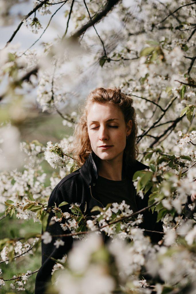 dromerig portret vrouw met bloesemboom, vrouw heeft ogen dicht