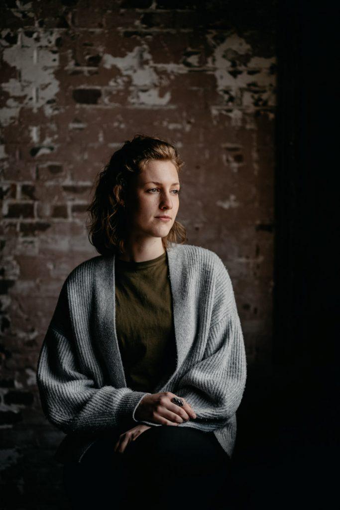 donker, sfeervol portret van vrouw, ze kijkt opzij
