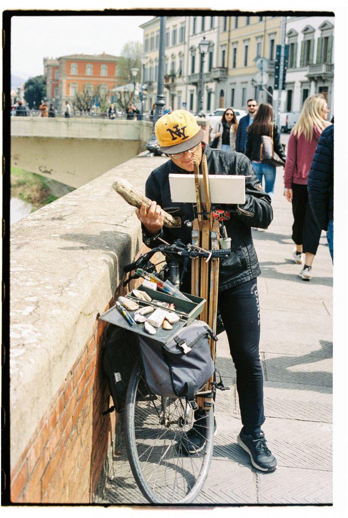 man schildert op een fiets in florence, italië