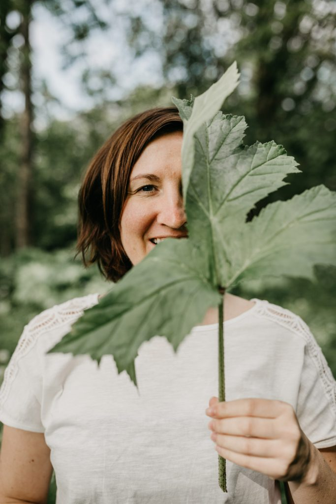 portret vrouw houdt groot boomblad voor haar gezicht