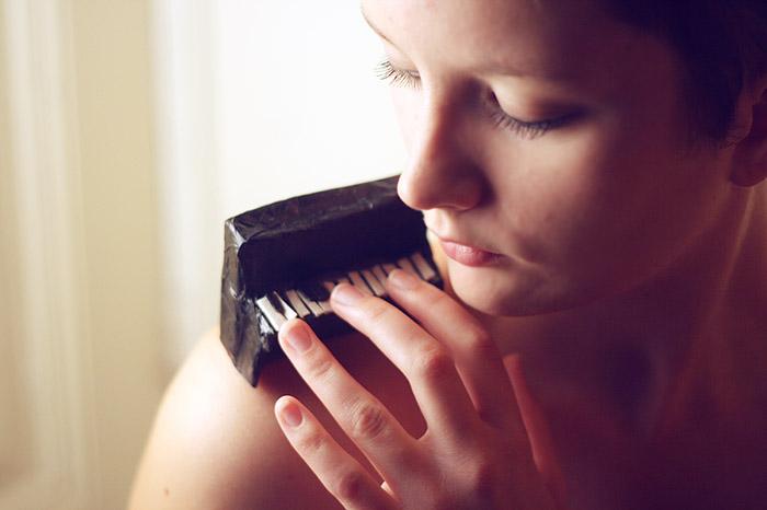 vrouw speelt miniatuur piano op schouder