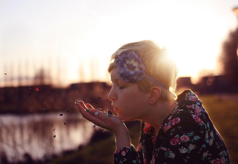 vrouw blaast confetti weg bij zonsondergang