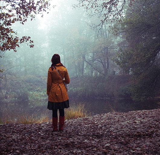 vrouw kijkt in de verte in de mist