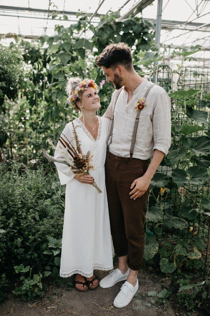 bruidspaar staat tussen planten in kas