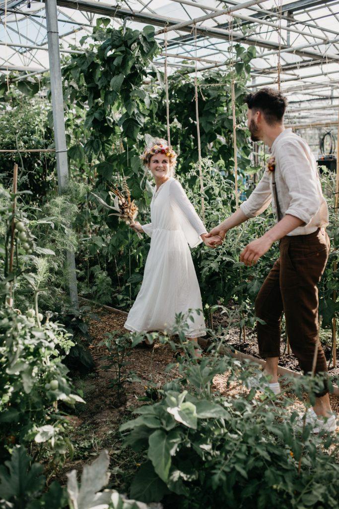 bruidspaar loopt hand in hand door kas