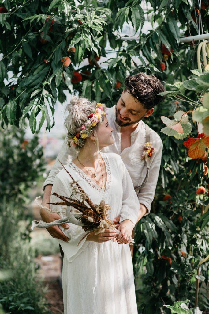 bruidspaar staat tussen perzikbomen in kas
