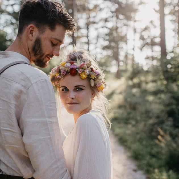 bruidspaar in bos, bruid kijkt in camera