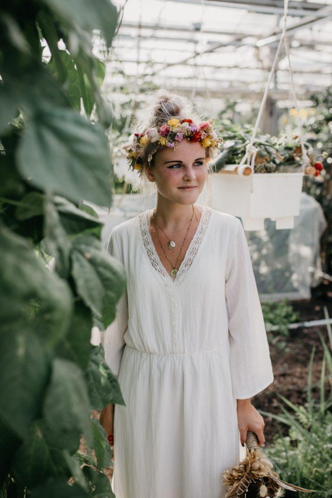 bruid met bloemenkrans staat in kas