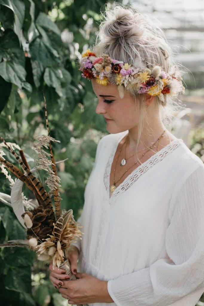 bruid kijkt naar boeket van gedroogde bloemen