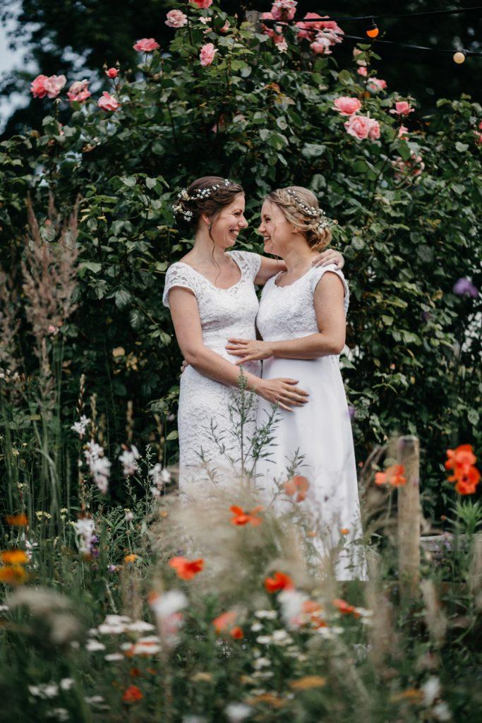 bruidspaar staat tussen de bloemen en poseert