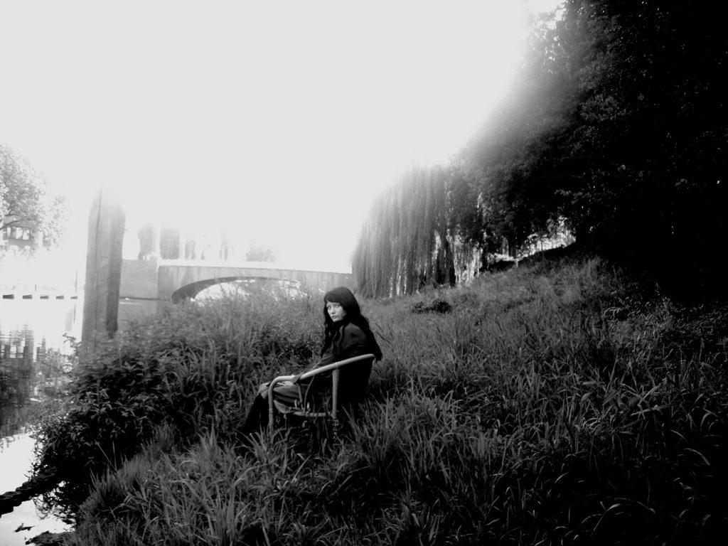 vrouw zit op stoel naast water, kijkt camera in