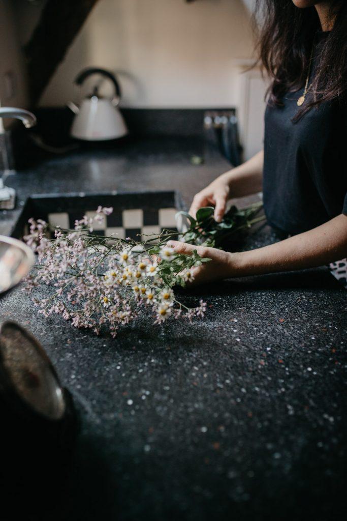 Bloemen op aanrecht worden door twee handen geschikt