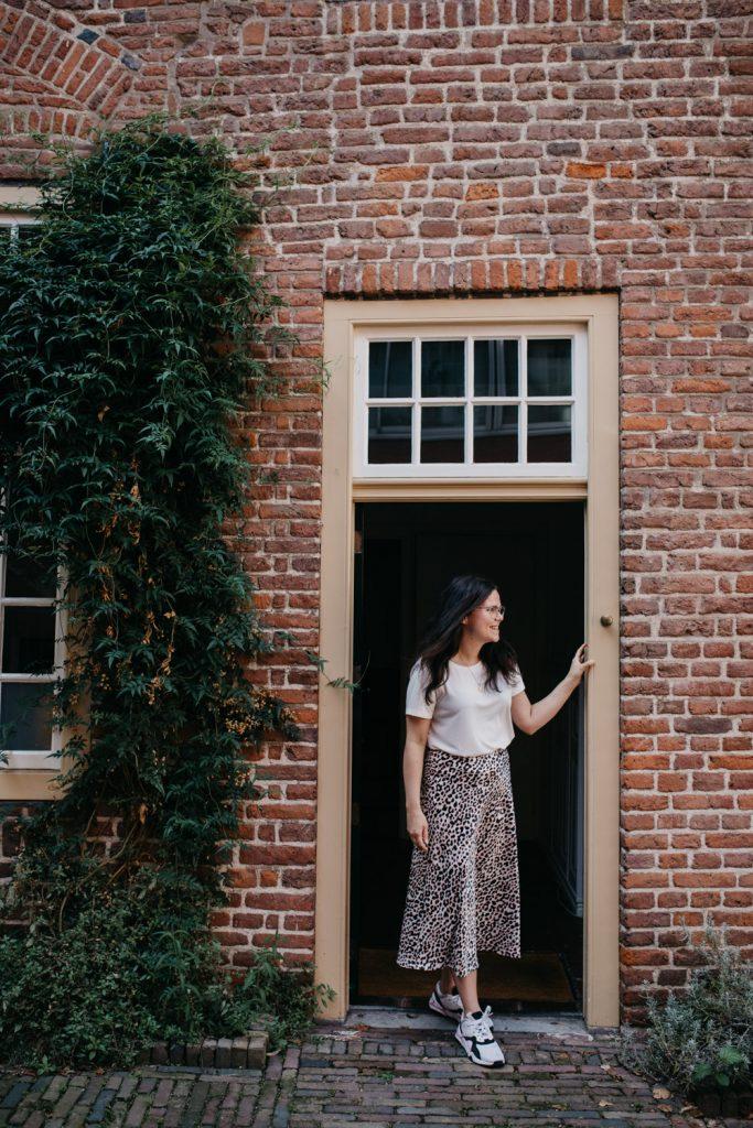 Vrouw staat in deuropening en kijkt opzij