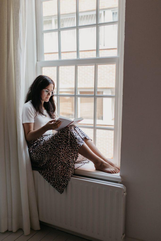 Vrouw leest boek zittend in het raam