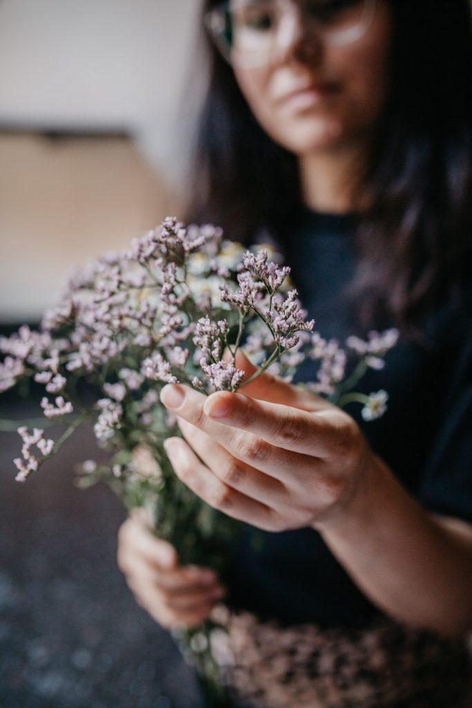 vrouw houdt bos bloemen vast, focus op hand