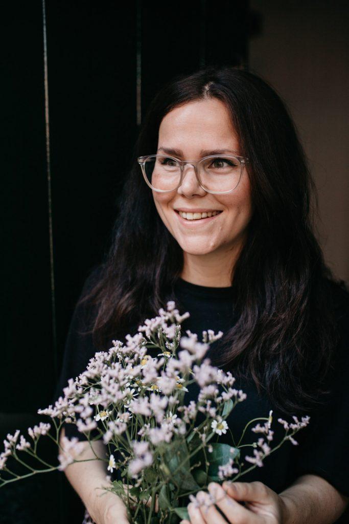Vrouw staat in deuropening met bos bloemen, kijkt weg