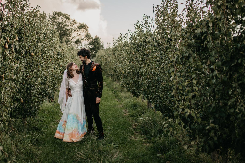 bruidspaar loopt door boomgaard