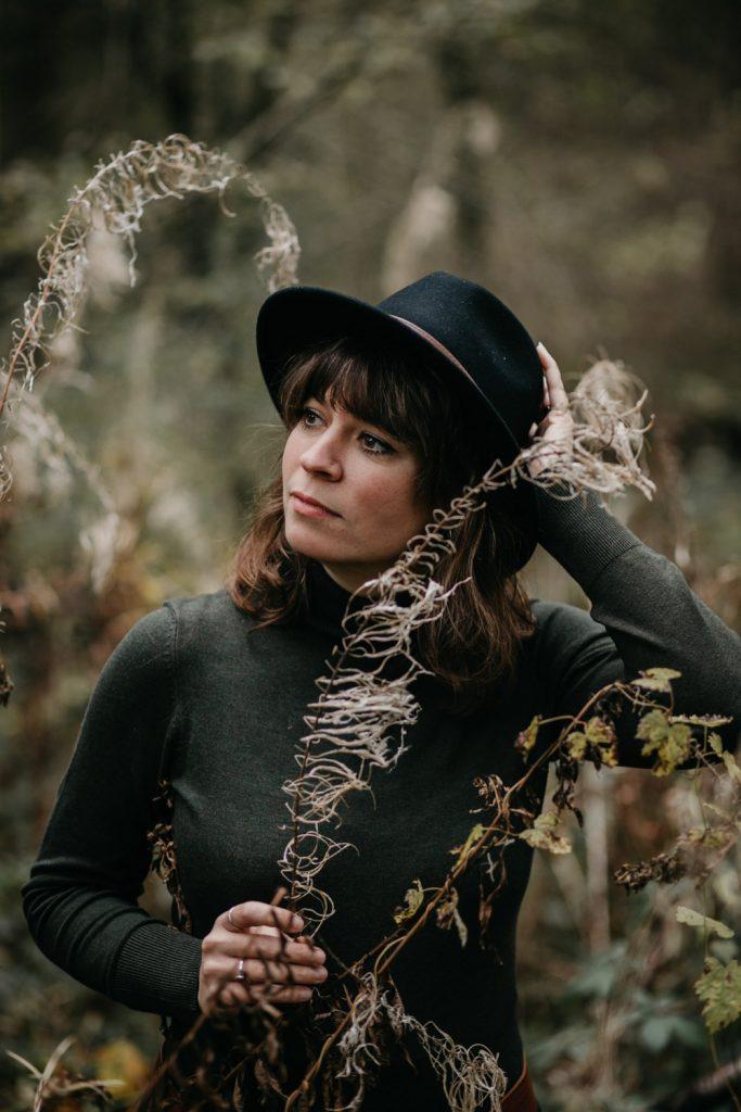 dame met hoed poseert tussen planten