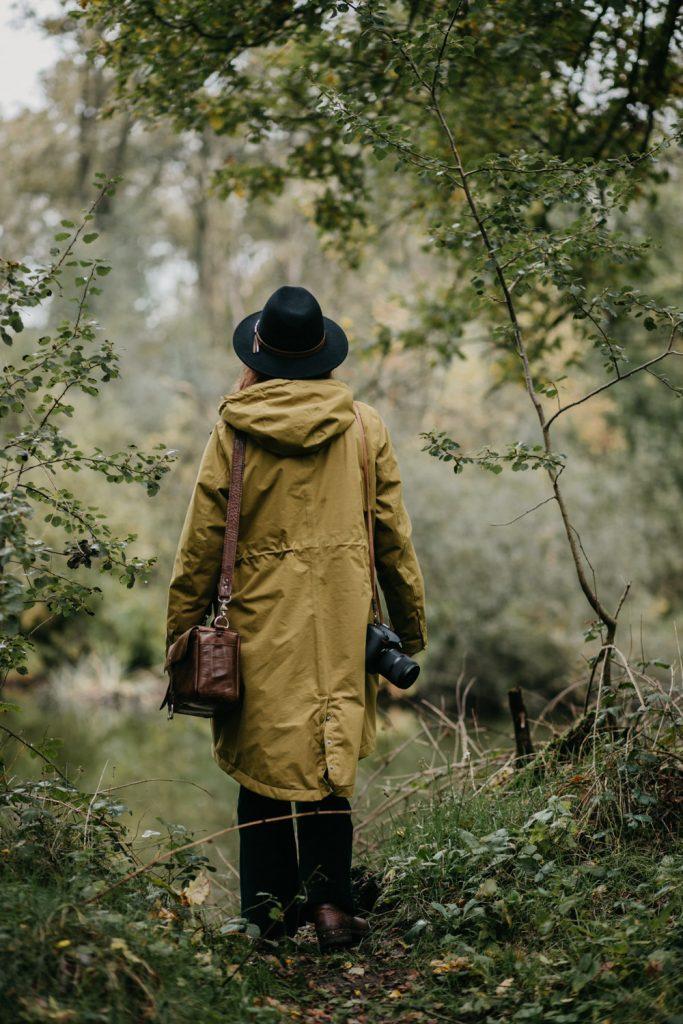 fotograaf eva staat in het bos met haar rug naar de camera