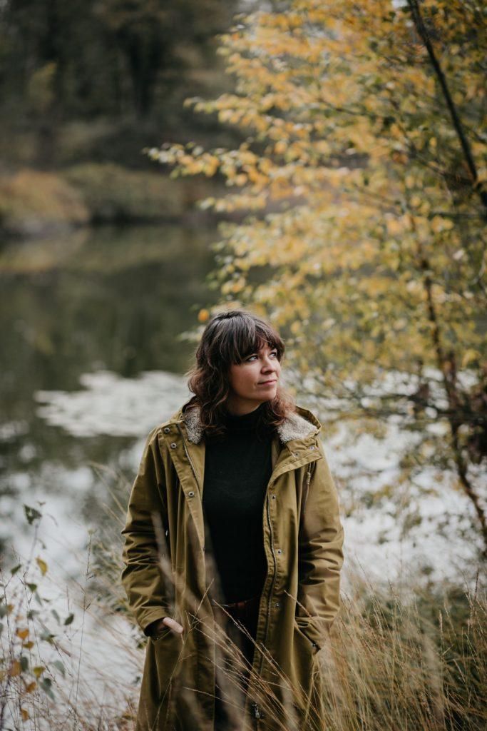 fotograaf eva staat in het bos, kijkt opzij