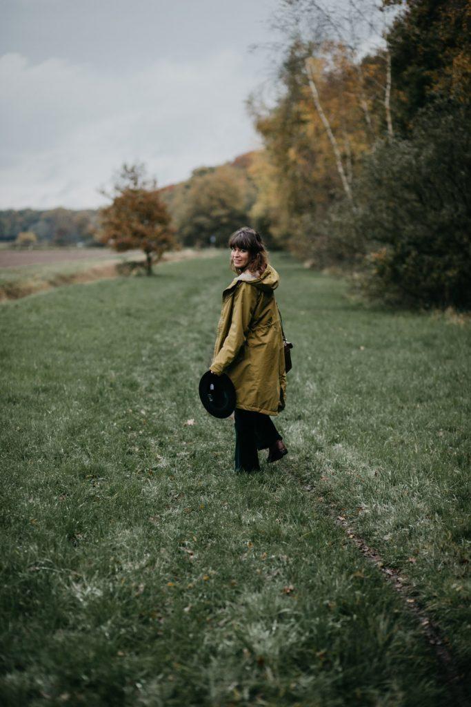 eva loopt door het gras en kijkt om naar de camera