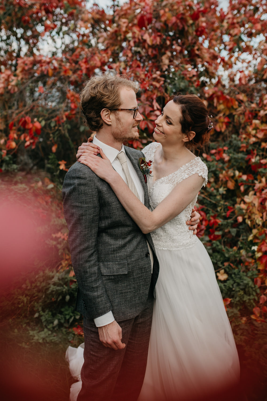 bruidspaar houdt elkaar vast voor boom in herfstkleuren