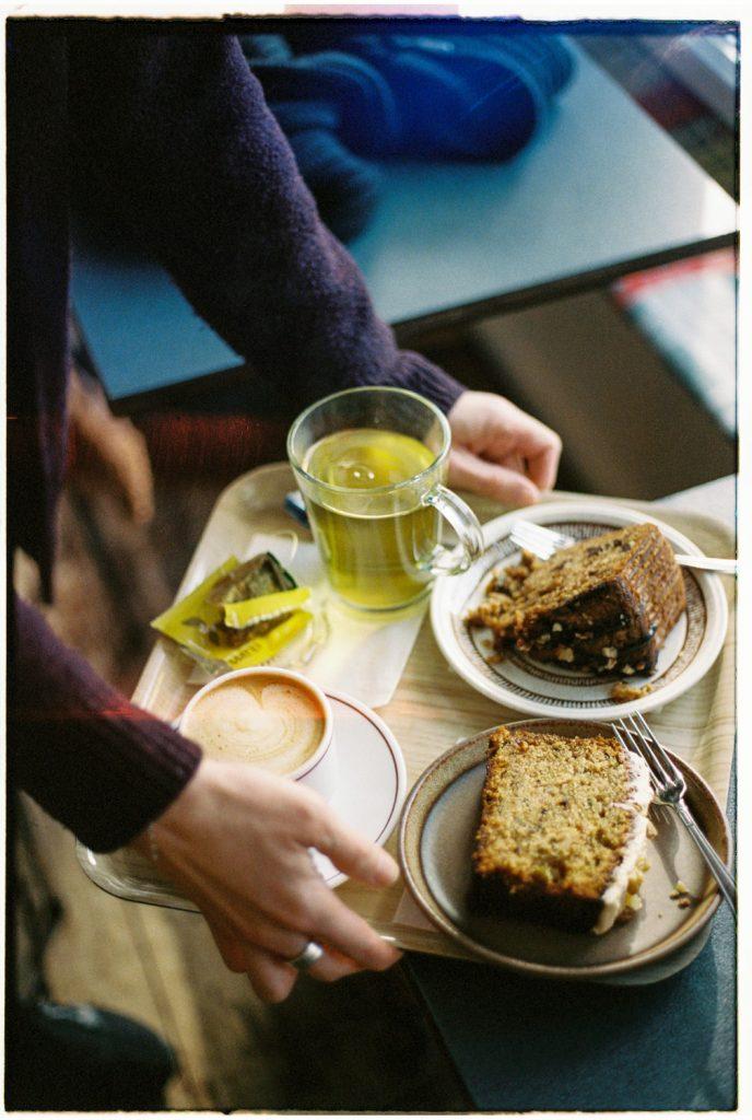 persoon zet dienblad neer met taart en thee