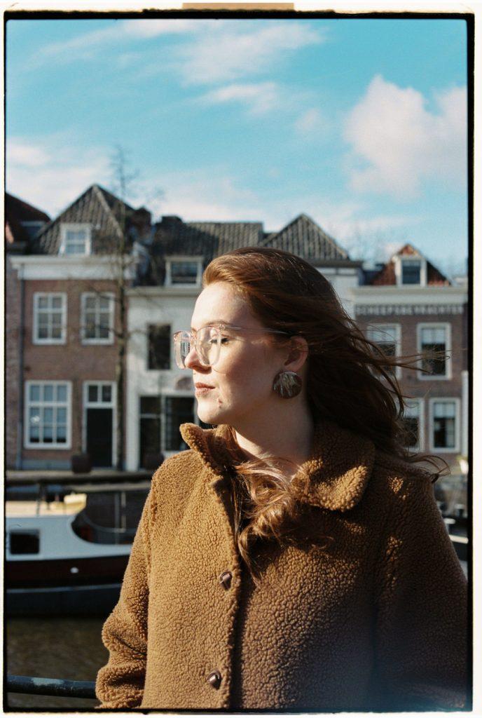 vrouw staat in de zon en geniet met ogen dicht