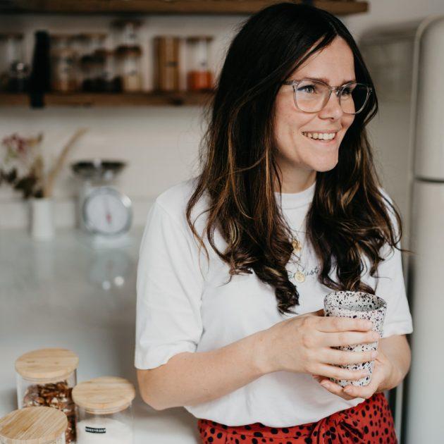 vrouw staat in de keuken en kijk lachend weg van de camera