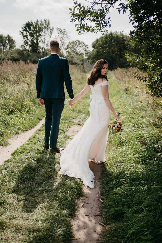 Bruidspaar loopt weg van camera, bruid draait om en kijkt naar camera