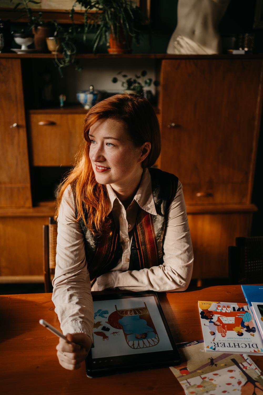 vrouw zit aan tafel, tekent op haar tablet en kijkt naar buiten
