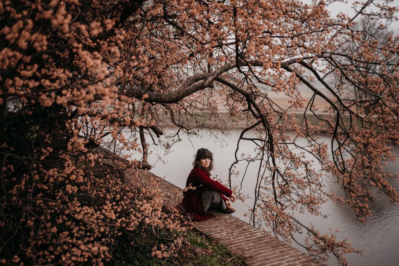 sfeerfoto van vrouw bij bloesemboom, vrouw kijkt in camera