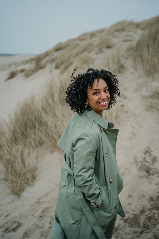 vrouw staat in de duinen en lacht naar de camera